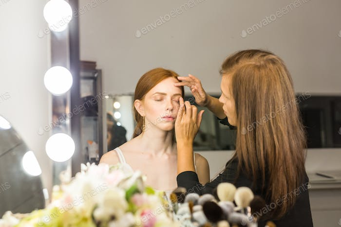 Professionelle Make-up-Künstler tun Glamour Modell Make-up bei der Arbeit