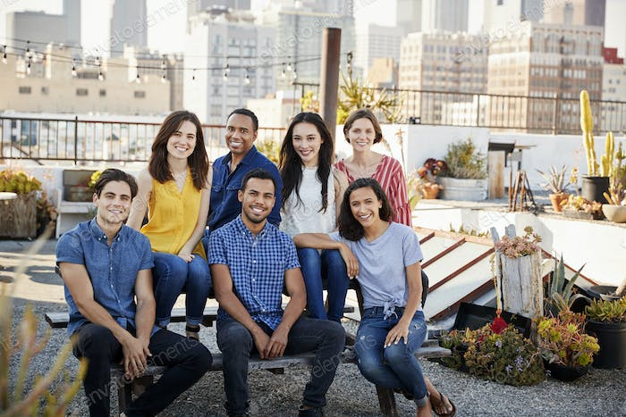 Portrait Of Friends Gathered On Rooftop Terrace For Party With City Skyline In Background