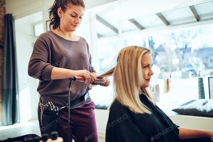 Hairdresser straightening a female client's hair in her salon