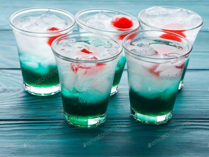 Kurze alkoholische grüne Getränke mit Kirsche