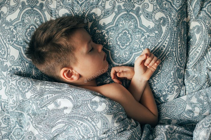 Adorable boy 6-7 years old sleeping in bed. Child having a good dreams.