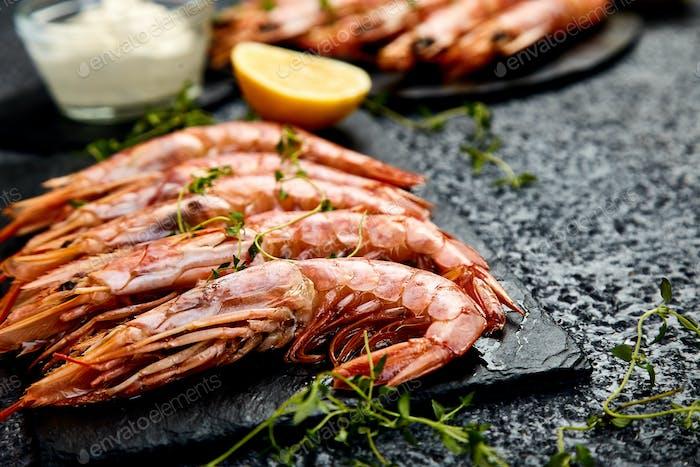 Grilled big tiger shrimps prawns on black slate plate