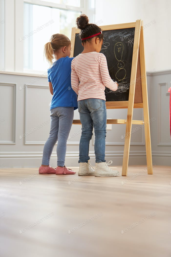 Two Girls Drawing Picture On Blackboard At Home