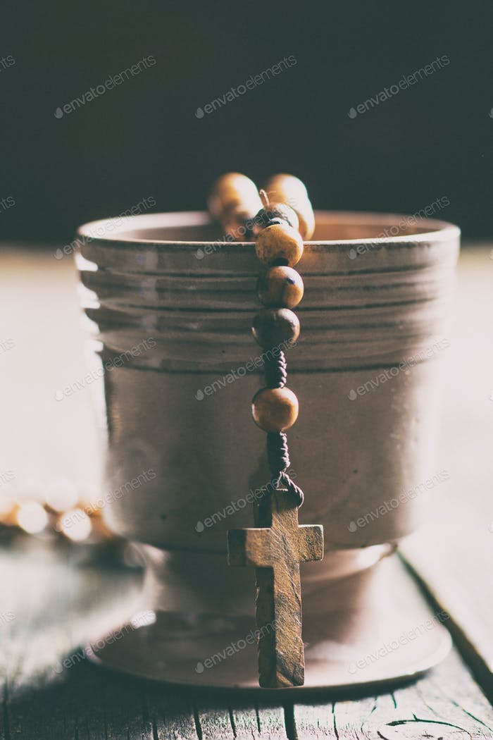 Rosary beads and cup of wine.