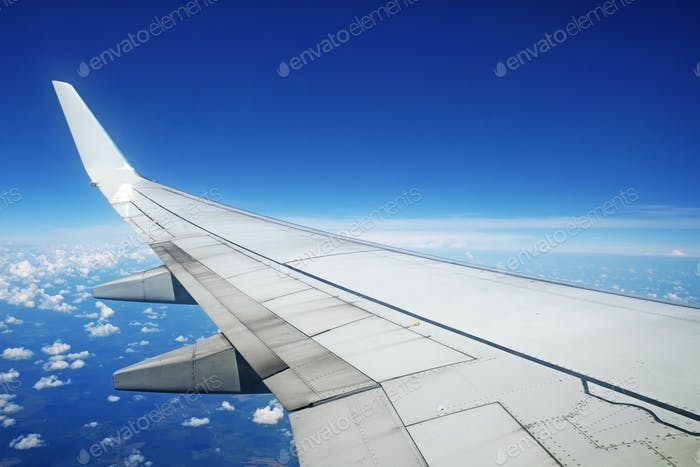 Airliner wing in flight on blue sky background