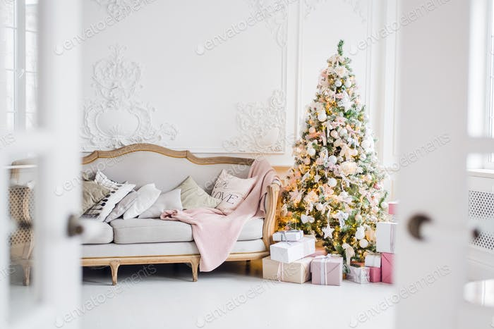 Christmas tree with a white sofa in a white room through the doorway