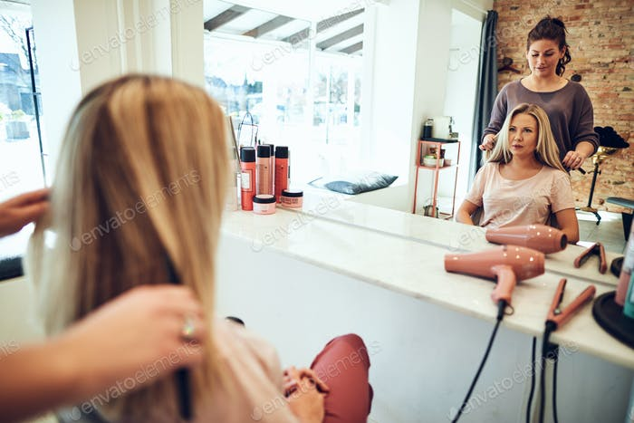 Woman looking in a salon mirror talking with her hairstylist