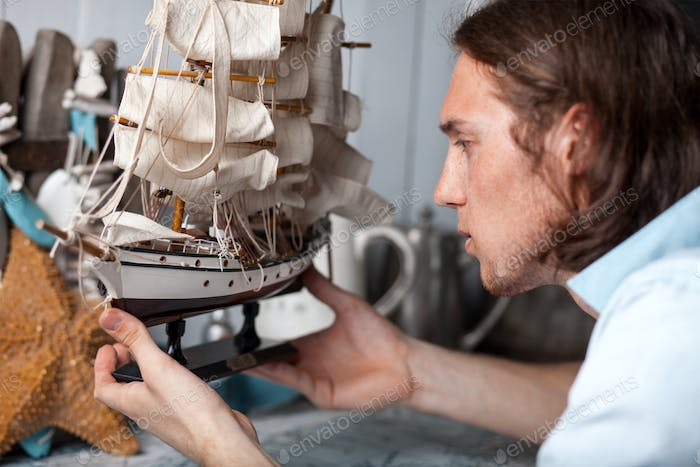 young man looks at model of sailing ship in vintage interior