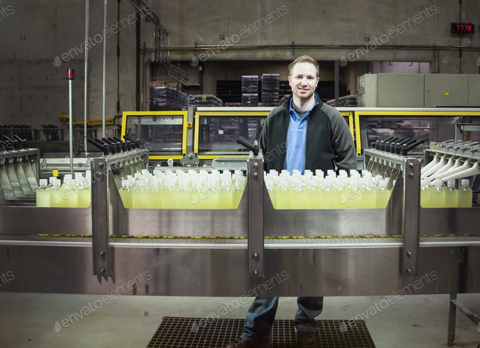 Man by to a conveyor belt of flavored water bottles in a bottling plant.