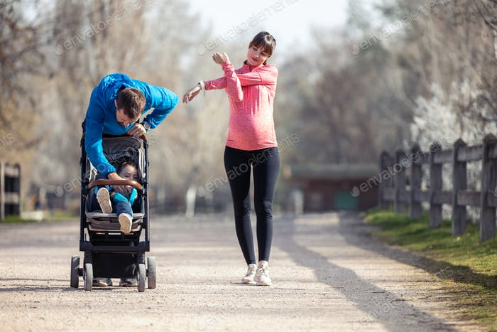 sporty young couple with her little son stretching while walking and enjoying the time together