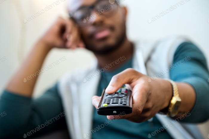 Handsome young black man watching tv at home.