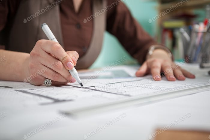 Close up of architect woman at her table drawing on blueprints