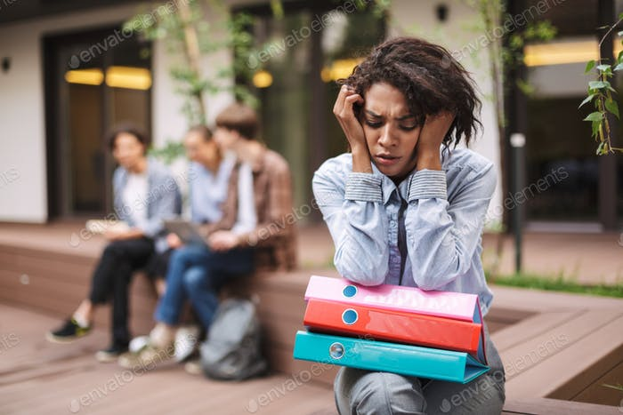 Portrait of upset lady sitting on bench with colorful folders on knees and sadly closing her eyes