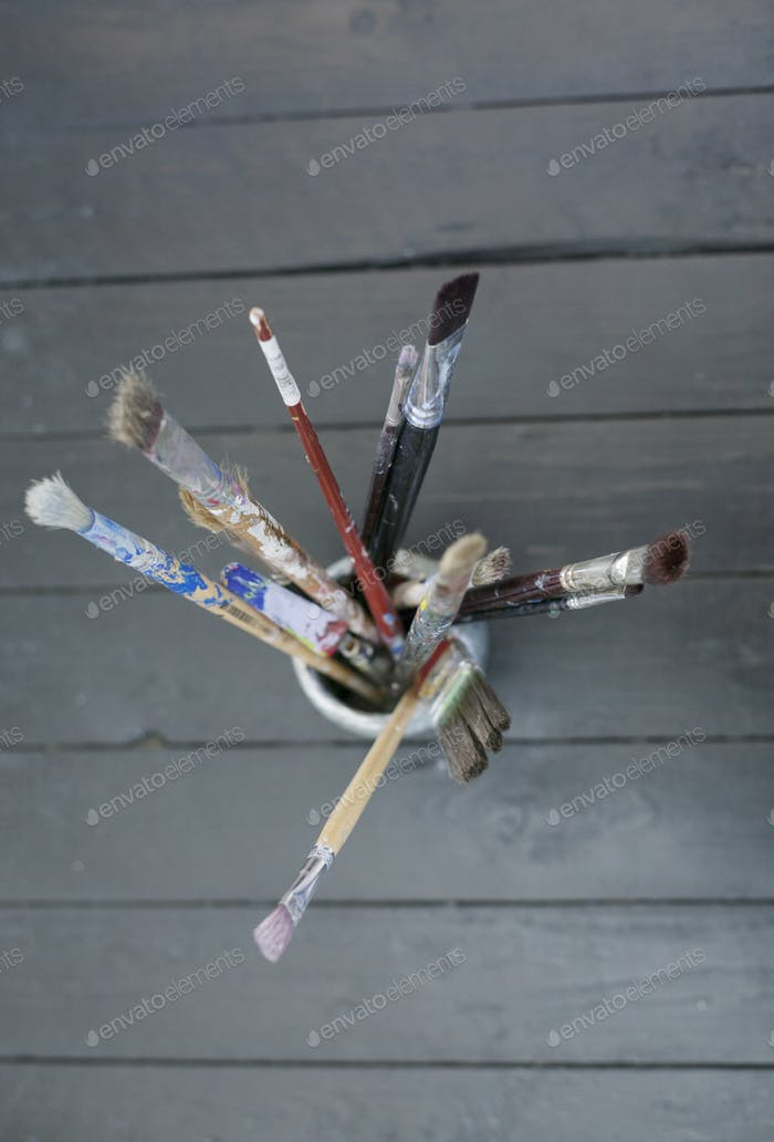 Directly above shot of paint brushes in container on floorboard