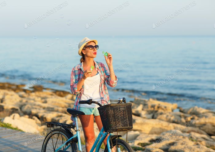 Carefree woman with bicycle standing on a wooden path at the sea