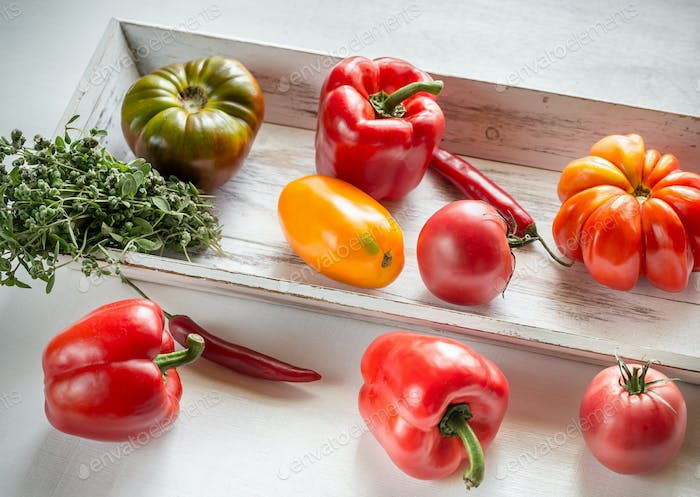 Fresh tomatoes and peppers on the wooden tray