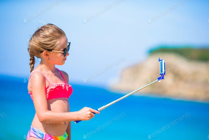 Little girl taking selfie by her smartphone on the beach. Kid enjoying her suumer vacation and