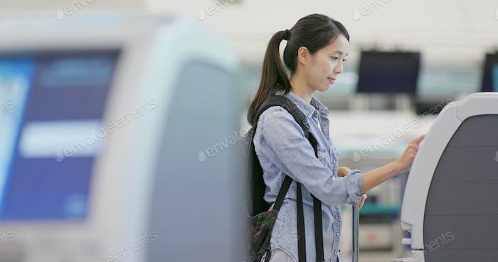 Frau mit Selfie Check-In Maschine am Flughafen