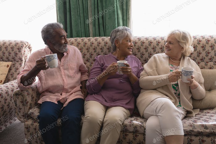 Front view of senior people interacting with each other while having coffee in living room at home
