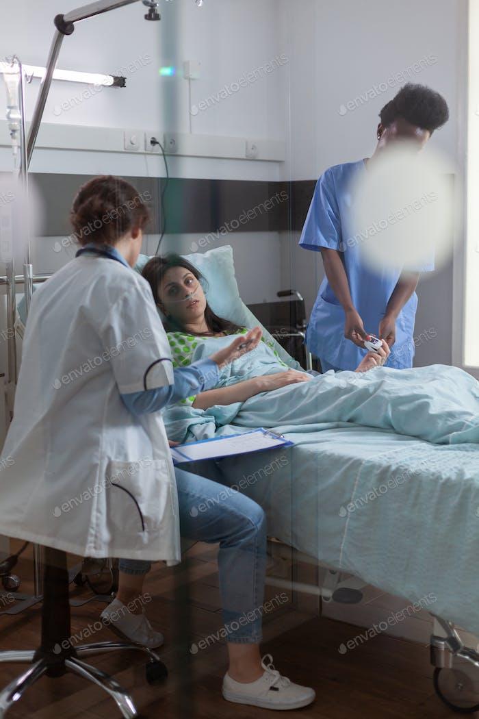 Medical team checking sick woman analyzing disease symptom