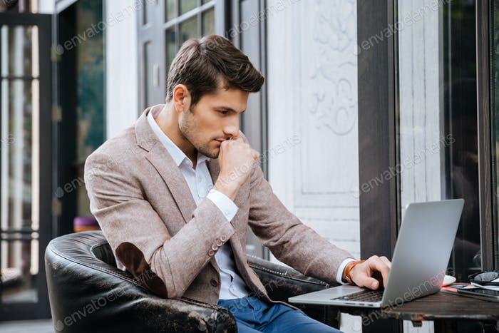 Businessman working on a laptop while sitting in cafe