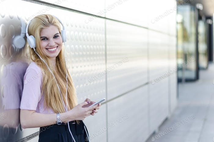 blonde woman isolated listening music with headphones and mobile phone outdoor
