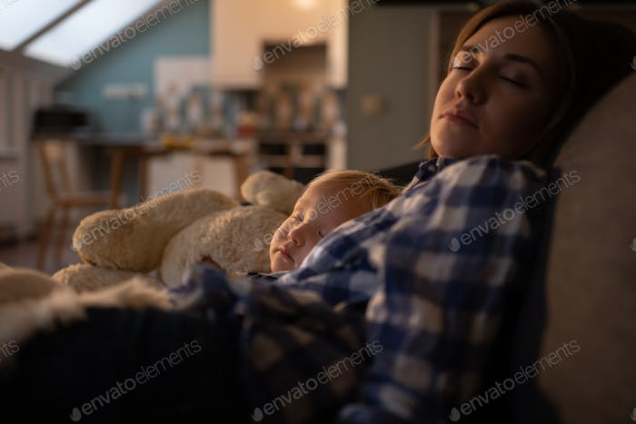 Mother sleeping with little cute son on couch at home