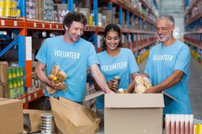 Happy volunteers tidy some goods in cardboard box