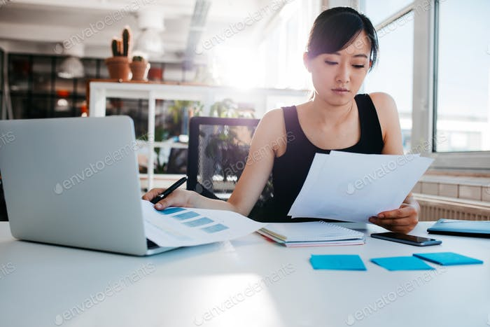 Businesswoman doing paperwork at her workplace