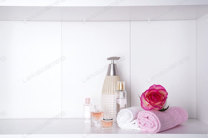 Stack of bath towels with rose on light background