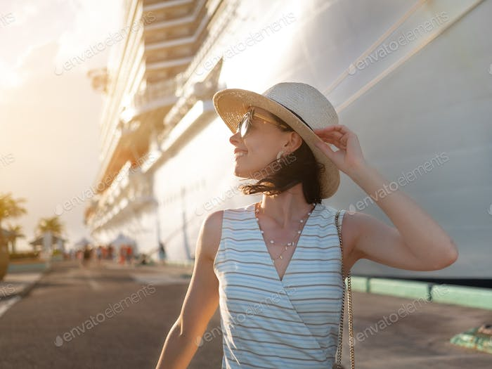 Happy young woman on the background of a white ship