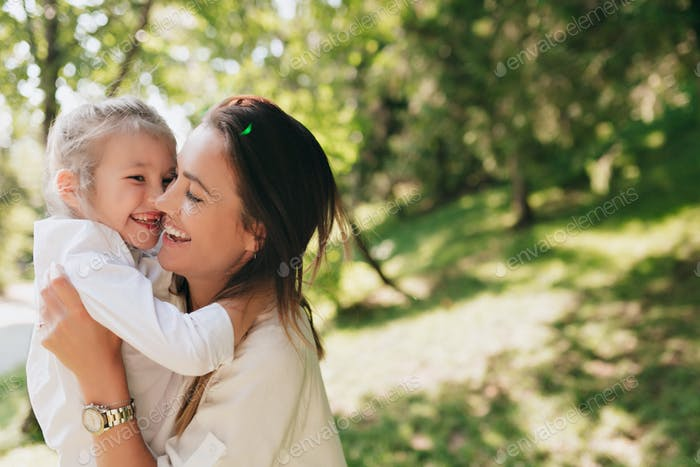 Little girl hugging mother and laugthing on blur nature background