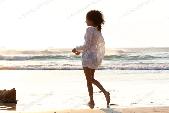 Attractive young woman walking on the beach barefoot