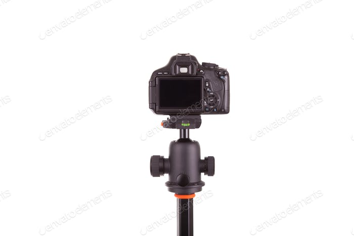Digital camera mounted on tripod, isolated on white background