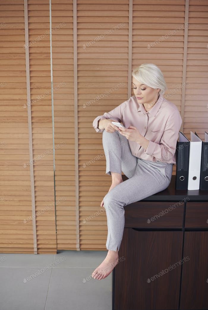 Barefoot woman sitting on drawer and texting