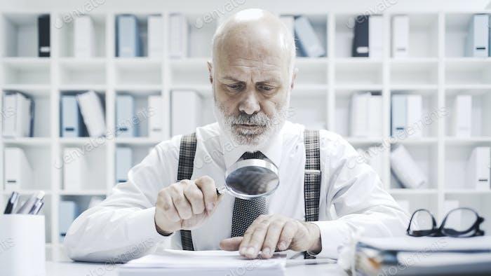 Корпоративный бизнесмен проверяет оформление документов с помощью лупы