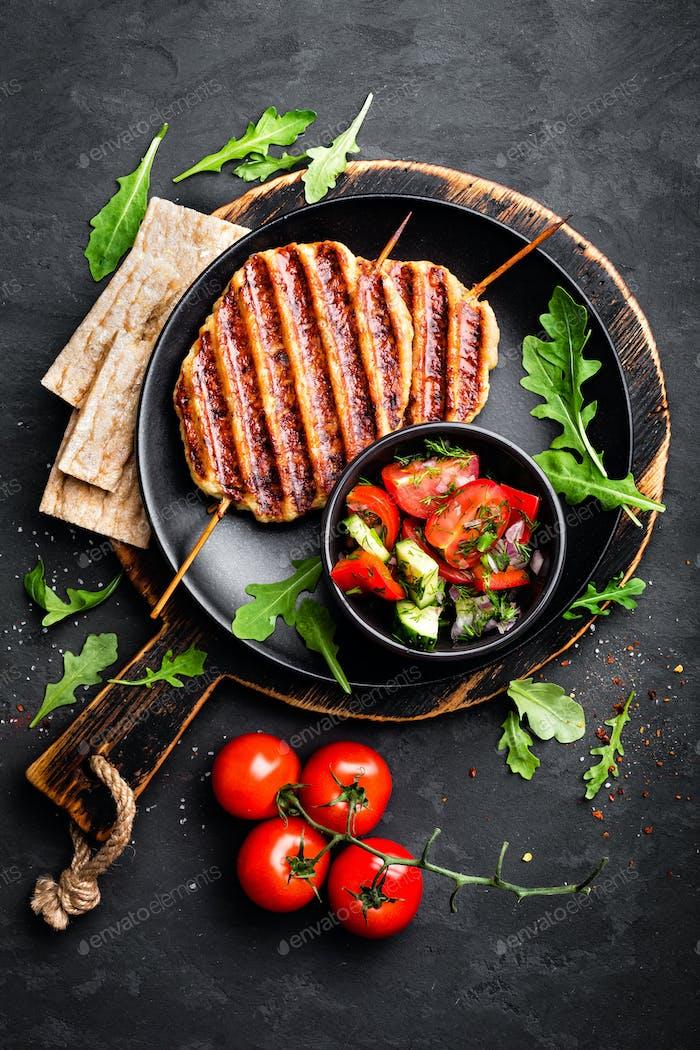 Juicy grilled chicken meat lula kebab on skewers with fresh vegetable salad on black background