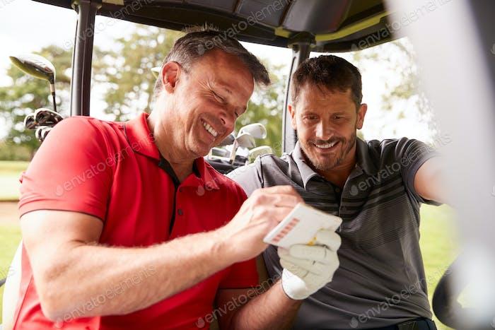 Zwei Reifen Männer spielen Golf Markierung Scorecard In Buggy Fahren entlang Kurs