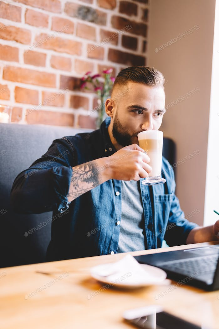 Man drinking coffee, looking at his laptop.