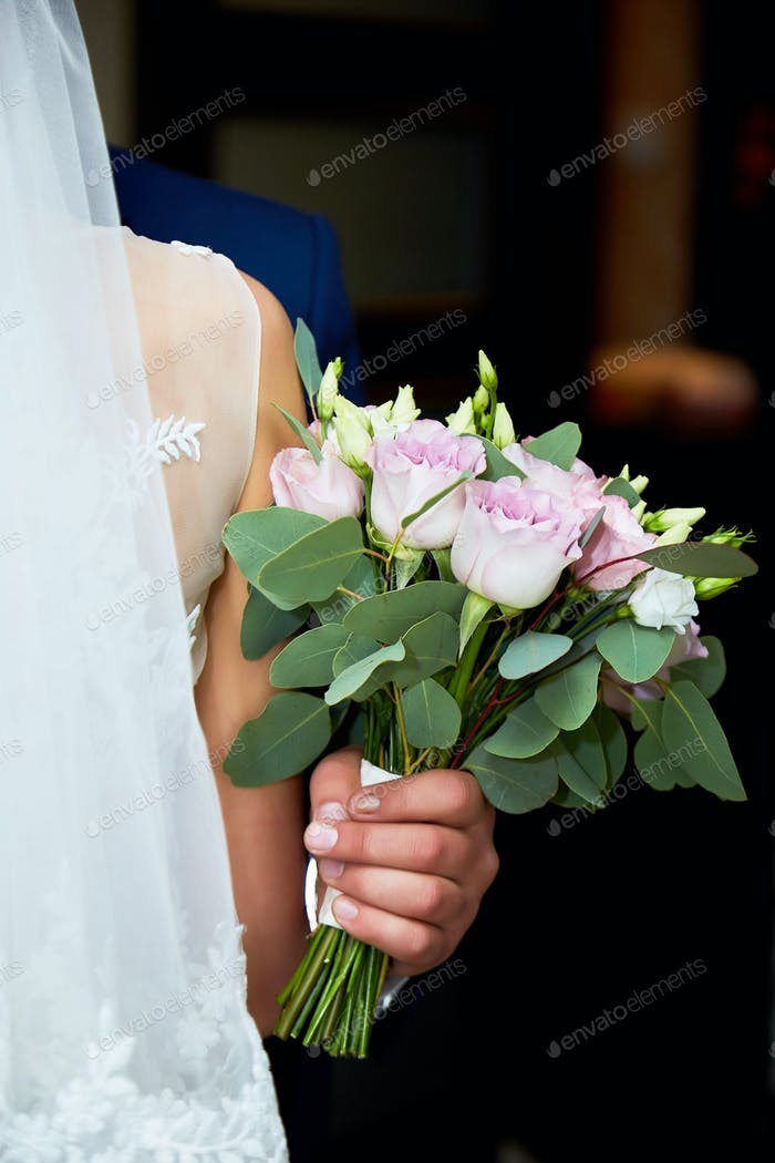 Bride in wedding dress and groom with a bouquet of flowers and greens in hands.