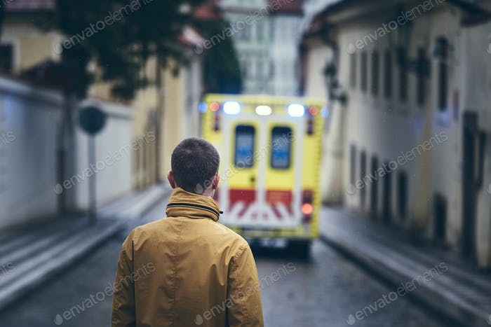 Man looking at leaving ambulance car