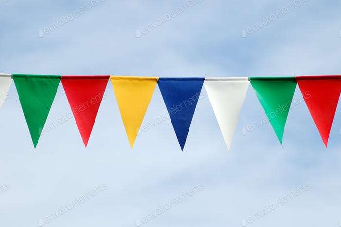 Colored triangular flags on blue sky background
