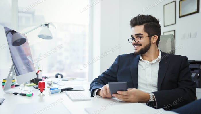 Businessman analyzing investment charts with calculator on office desk