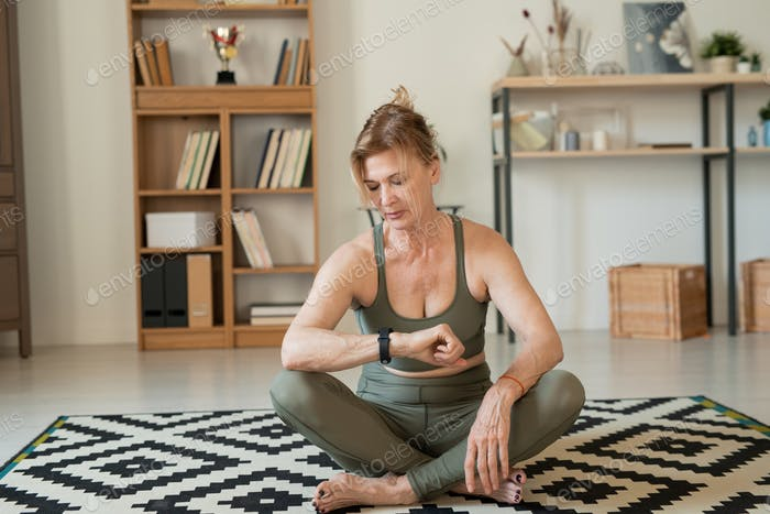 Serious mature sportswoman in tracksuit looking at smartwatch after home workout