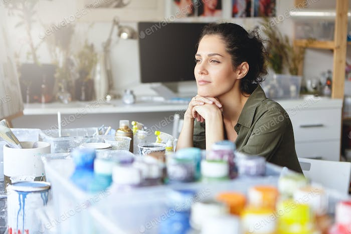Beautiful female artist with thoughtful expression, sitting at her workplace with watercolors, tryin