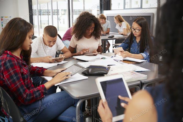 Lehrer sitzen mit Gymnasiasten mit Tabletten