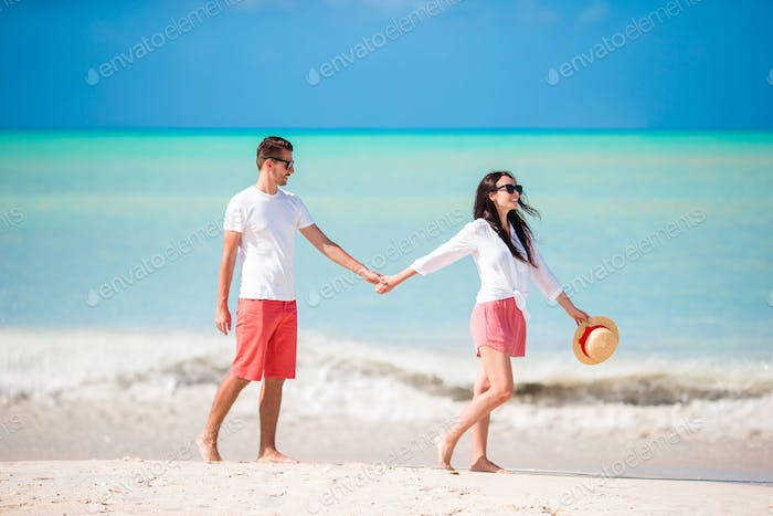 Young couple on white beach. Happy family on honeymoon vacation