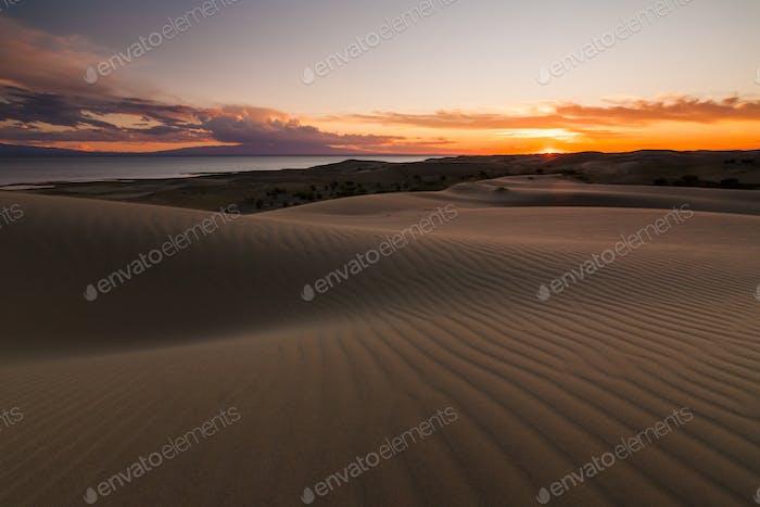 Sanddünen auf dem Hintergrund des Wüstensees. Gobi Wüste