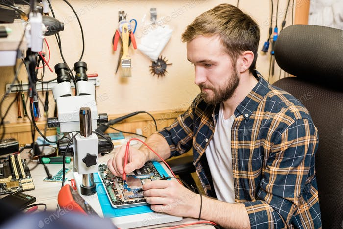 Young serious mechanic with two soldering-irons repairing demounted touchpad