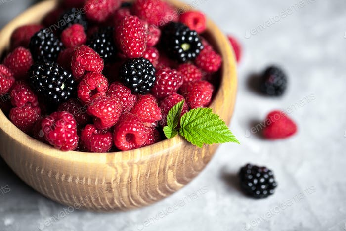 raspberries and blackberries in wood bowl on gray table, vintage